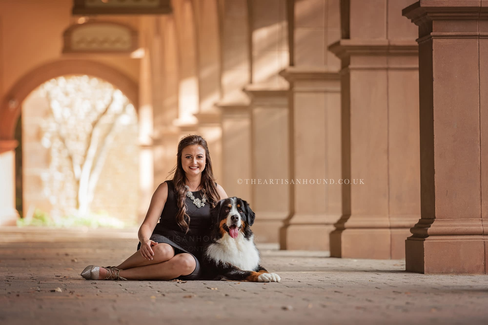 Bernese mountain dog and owner sitting in walkway with columns