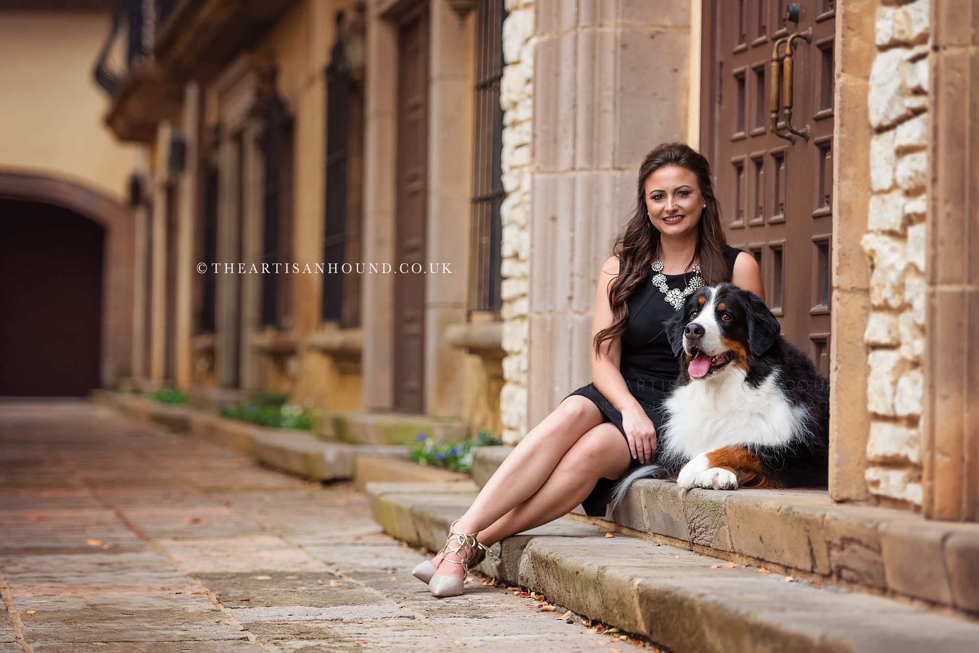 Berner dog and woman sitting on steps by door