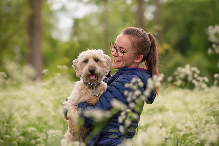woman smiling holding cream coloured terrier dog in field