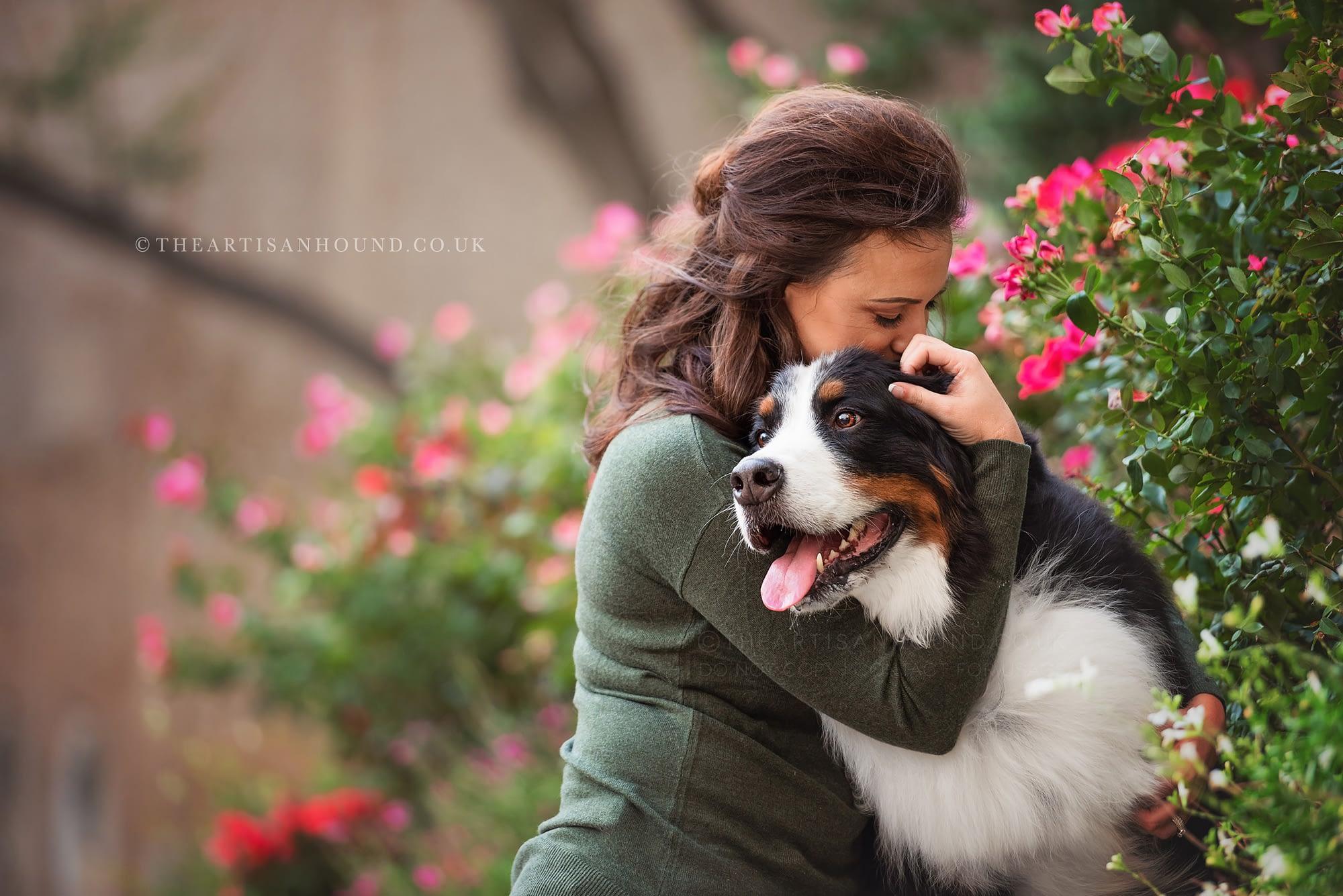Owner cuddling dog near flowers