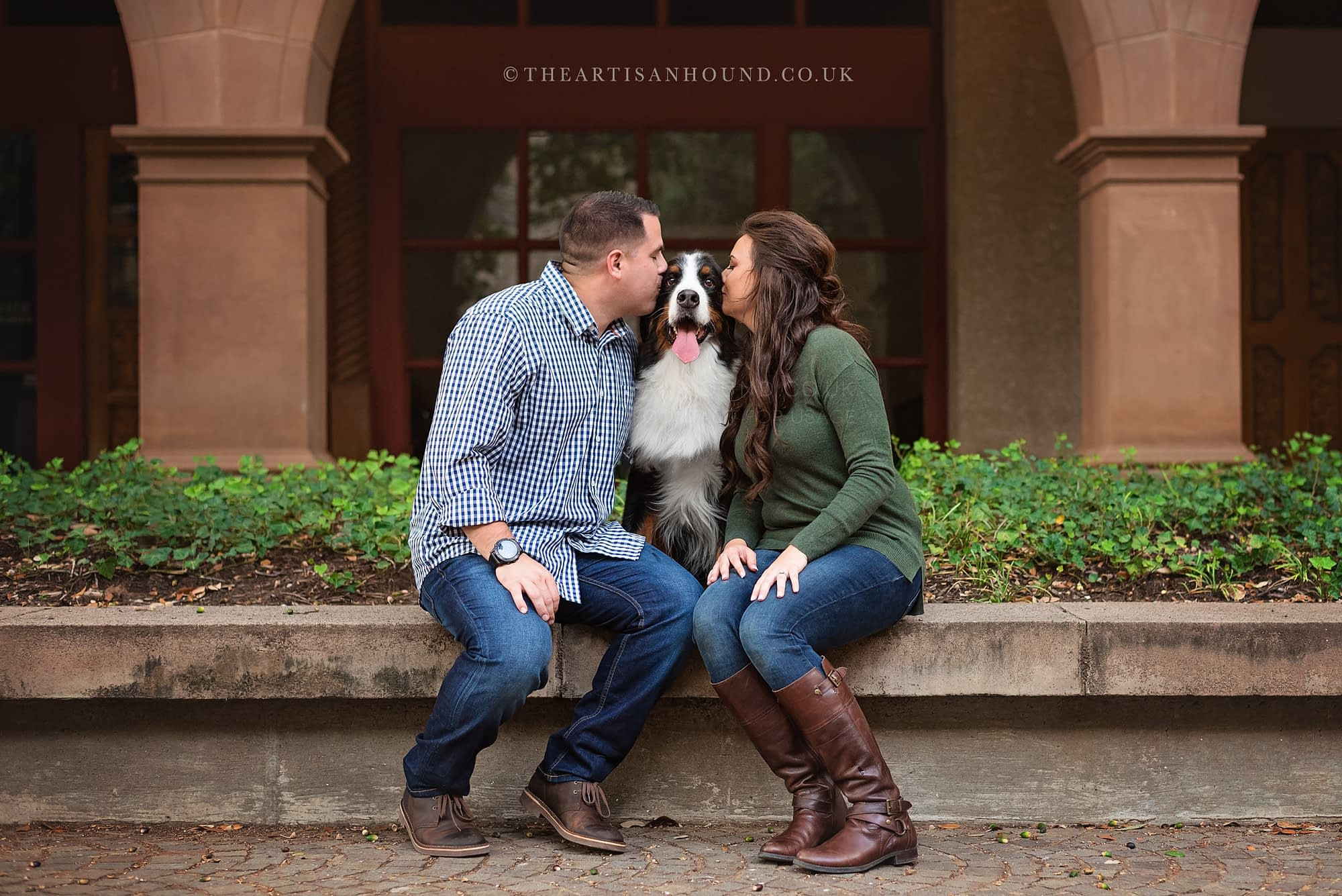 Man and woman kissing Bernese Mountain Dog